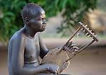 A man plays a homemade masankop in Mundri, South Sudan.