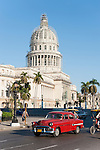 Havana, Cuba; a red classic 1956 Chevy serves as a taxis and share the road with bicycle taxis during the morning commute along Paseo de Marti, with the Capitol building in the background