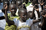Children link hands as they sing during an outdoor Mass in Christ the King Catholic parish in Malakal, Southern Sudan, on November 21, 2010.