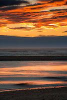 Intense sunset over Tasman Sea at Hokitika River mouth, South Westland, West Coast, New Zealand