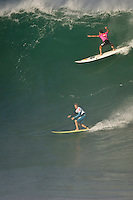 """WAIMEA BAY, Oahu/Hawaii (Tuesday, December 8, 2009) Carlos Burle (BRA) and Jamie O'Brien (HAW) share a wave. - The Quiksilver In Memory of Eddie Aikau,  was officially  called """"ON"""" by Contest Director George Downing this morning. The ASP specialty sanctioned event kicked off at 8am with wave face heights in the 25-35-foot range..Nine times world champion Kelly Slater (USA) led for most of the day until Greg Long(USA) scored his best four scoring rides in the last heat of the day to over take Slater. Long scored a perfect 100 point wave late in the day to seal the first prize purse of $55,000. Slater was runner up with Sunny Garcia (HAW) in 3rd, defending champion Bruce Irons (HAW) 4th and Ramon Navarro (CHL)  in 5th place. Navarro won the Monster drop award for the biggest drop, also in the final heat of the day when wave faces were pushing 40' plus...The northern hemisphere winter months on the North Shore signal a concentration of surfing activity with some of the best surfers in the world taking advantage of swells originating in the stormy Northern Pacific. Notable North Shore spots include Waimea Bay, Off The Wall, Backdoor, Log Cabins, Rockpiles and Sunset Beach... Ehukai Beach is more  commonly known as Pipeline and is the most notable surfing spot on the North Shore. It is considered a prime spot for competitions due to its close proximity to the beach, giving spectators, judges, and photographers a great view...The North Shore is considered to be one the surfing world's must see locations and every December hosts three competitions, which make up the Triple Crown of Surfing. The three men's competitions are the Reef Hawaiian Pro at Haleiwa, the O'Neill World Cup of Surfing at Sunset Beach, and the Billabong Pipeline Masters. The three women's competitions are the Reef Hawaiian Pro at Haleiwa, the Gidget Pro at Sunset Beach, and the Billabong Pro on the neighboring island of Maui...Photo: Joliphotos.com"""