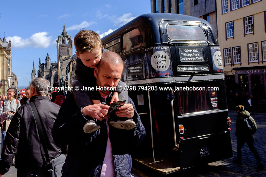Edinburgh, UK. 15.04.2017. A boy rides on his father's shoulders whilst they pass a ghost tours bus, on the Royal Mile. Photograph © Jane Hobson.