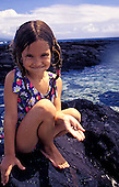 A small girl on the rocks of a tidepool in Kona smiles while holding small shells in her palm.