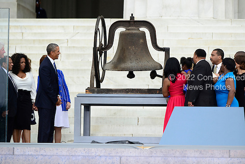 Ambassador Andrew Young, Oprah Winfrey, and United States President Barack Obama look on as members of the late Dr. Martin Luther King, Jr's family ring the bell from the 16th Street Baptist Church in Birmingham, Alabama at the Let Freedom Ring ceremony on the steps of the Lincoln Memorial to commemorate the 50th Anniversary of the March on Washington for Jobs and Freedom.<br /> Credit: Ron Sachs / CNP