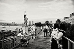 Tourists take photos in front of the copy of the Statue of Liberty in Tokyo, Japan.