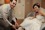 Taiwanese Wedding -- The groom helping the bride out of her shoes so she can comfortably relax.