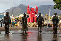 "South Africa, Cape Town.  Nobel Square Statues of Albert Luthuli, Desmond Tutu, FW de Klerk, and Nelson Mandela.  Sculptor Claudette Schreuders.  In background is the ""Lego Man"" sculpture made of 4200 plastic  Coca Cola crates.  Designed by Porky Hefer."