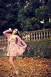 A pretty brunette in a pastel floral dress and pink sweater posing in a park.
