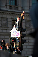 Protestors stand on top of traffic lights during a student demonstration in Westminster, central London on the day the government passed a bill to increase university tuition fees.