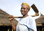 A woman displaced by years of conflict in northern Uganda heads out to work her field.