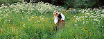 Estonian girl gathering flowers on the wooodland's edge