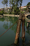 Wooden piles with rusty chain in canal, Lido, Venice Lagoon,Italy.