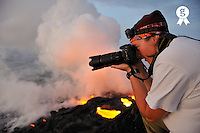 Woman photographing lava flowing to the sea (Licence this image exclusively with Getty: http://www.gettyimages.com/detail/84430557 )