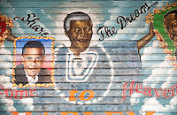 """A mural on a security gate in Harlem in New York on a rainy Friday, December 6, 2013 shows a memorial to the late Nelson Mandela. The painting by """"Franco the Great"""" also shows Pres. Barack Obama and other black personalities. The South African civil rights activist passed away at the age of 95. Mandela visited Harlem in 1990 on his first visit to New York. (© Richard B. Levine)"""