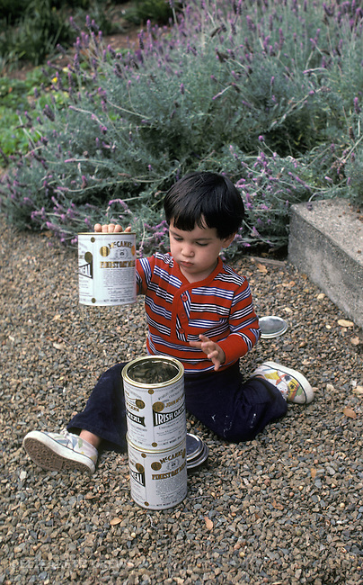 Berkeley CA Boy, twenty-one months old building with oatmeal cans, filling them with gravel  MR