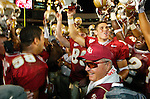 While his Seminole team does a chant with helmets raised, coach Bobby Bowden flashes a smile after Michael Boulware (L) and Chris Rix (R) presented him with a commemorative football declairing him the winningest Division 1 active college football coach in America after winning game number 339 against Wake Forest in Tallahassee, Florida October 25, 2003. (Mark Wallheiser/TallahasseeStock.com)