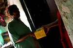 INDIA (West Bengal - Calcutta) -A CBO worker hands over a box of Condom to a sex worker in Munsigaunge, Kolkata. As most of the customers are unaware of HIV and STDs they offer more money for not using condom. Sometimes the sex worker has to allow to keep the goodwill and have unprotected sex . - Arindam Mukherjee