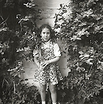 Young girl with flowers in front of vine. 1976