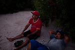 """Two fishermen relax after a day of fishing near Pueblo Viejo de San Dionisio...The Isthmus of Tehuantapec, long a center for indigenous land ownership, is now embroiled in a land dispute over wind farm land...Called """"Mexico's little waist,"""" the Isthmus is a wind tunnel that links the Gulf of Mexico to the Pacific through mountain passes at the narrowest part of Mexico. The geographical funnel makes it one of the windiest places in North America and for a decade wind energy companies have been jostling to acquire land to power the likes of Coca-Cola and Wal Mart."""