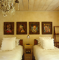 In this bedroom the twin beds are covered in crisp white quilts with matching scatter cushions and the wall is decorated with African paintings