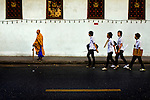 A Buddhist monk waits for a taxi on a curb outside Mahatchulalong University in Bangkok, Thailand, Southeast Asia as a group of students passes by.