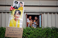 People look through the window as Nobel Peace Prize winner Aung San Suu Kyi arrives at Nationality Verification Centre for migrant workers from Myanmar in Samut Sakhon province May 31,2012. Suu Kyi received a rapturous reception in Thailand from crowds of cheering compatriots who flocked to celebrate her first trip outside Myanmar in nearly a quarter of a century.  REUTERS/Damir Sagolj (THAILAND)