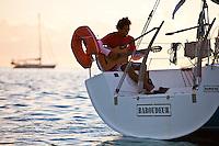 Man playing guitar on yacht at sunrise in lagoon off Tahaa Island