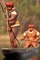 Body-painted Yaulapiti Indians in canoe fishing with bow and arrow at Tuatuari river in Xingu National Park, Amazon rainforest.