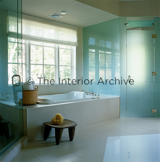 This contemporary bathroom has a floor of pale limestone and an enclosed shower of opaque glass