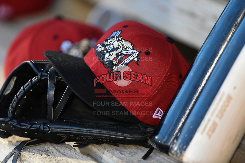Batavia Muckdogs hat, glove and bats sit on the dugout bench during a game against the Auburn Doubledays on June 16, 2014 at Dwyer Stadium in Batavia, New York.  Batavia defeated Auburn 4-3.  (Mike Janes/Four Seam Images)