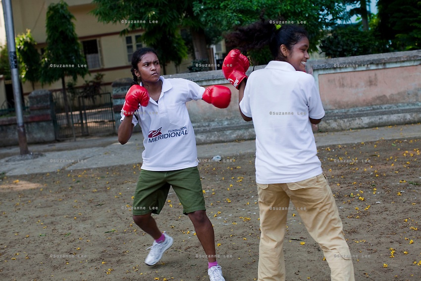Razia Shabnam (unseen) conducts a boxing training session with a group of girls from an NGO in a park in Basduni, Tolly Gunge, Calcutta, West Bengal, India. Razia Shabnam, 28, was one of the first women boxers in Kolkata. She was also the first woman in her community to go to college. She is now a coach and one of only three international female boxing referees in India.  Photo by Suzanne Lee for Panos London