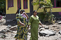 Women walk beside a family home surrounded by debris after it was struck by the tsunami. More than 170 people died when a tsunami triggered by an 8.3 magnitude earthquake hit Samoa and neighbouring Pacific islands on 29/09/2009. Samoa (formerly known as Western Samoa)..