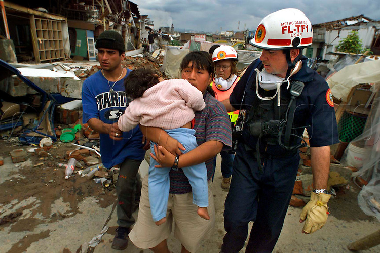 1/30/99 AL DIAZ/HERALD STAFF--Claudia Patricia Fernandez walks her son, Wilson Andres Garzon, 2,  with assistance from Miami-Dade Fire Rescue's Urban Search and Rescue Team member, Lt. Roman Bas, Sally Williamson at rear as friend Miller Mu–oz holds the boys hand. The boy was rescued out of his home on Monday after falling five floors head first suffering a head injury during Monday's earthquake in Armenia, Colombia. Four days latter the rescue team's Dr. Robert Del Cristo examined the child and determined he needed immediate medical care.