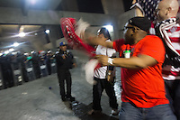 USA fans celebrate while being escorted by Mexican police officers in riot gear after the USA tied Mexico at their World Cup Qualifier at Azteca stadium in Mexico City, Mexico on March 26, 2013.
