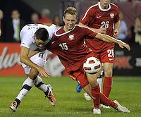 US forward Clint Dempsey battles for the ball with Poland midfielder Adam Matuszczyk (15).  The U.S. Men's National Team tied Poland 2-2 at Soldier Field in Chicago, IL on October 9, 2010.