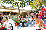 Anjali Sharma, 5, prepares to jump through a rope as her brother and mom power the a string bike during a display in downtown Los Altos hosted by The Exploratorium museum.