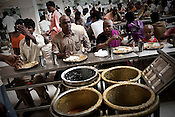 Hindu Devotees with shaved heads are seen eating the prasad at The Sai Prasadalaya in Shirdi, Maharashtra, India. The prasadalaya feeds an approximate number of 30000 Sai Baba devotees as a Prasad (holy meal). Free Prasad meals are served to all the devotees. An approximate number of 1000 devotees are served everyday with this facility. Expenses for a plate of Prasad meal  is around Rs. 15/- but the Saibaba Sansthan provides prasad meals to all Sai devotees to Rs. 6/- only. The prasadalaya at the Shirdi Sai Baba Shrine is powered by a large array of concave mirrors that transform sunlight to energy to create hot water and steam for the cooking process. Photograph: Sanjit Das