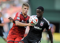 Washington D.C. - July 30, 2014: Eddie Johnson (7) of D.C. United goes against Nick Hagglund (17) of Toronto FC.  D.C. United defeated the Toronto FC 3-1 during a Major League Soccer match for the 2014 season at RFK Stadium.