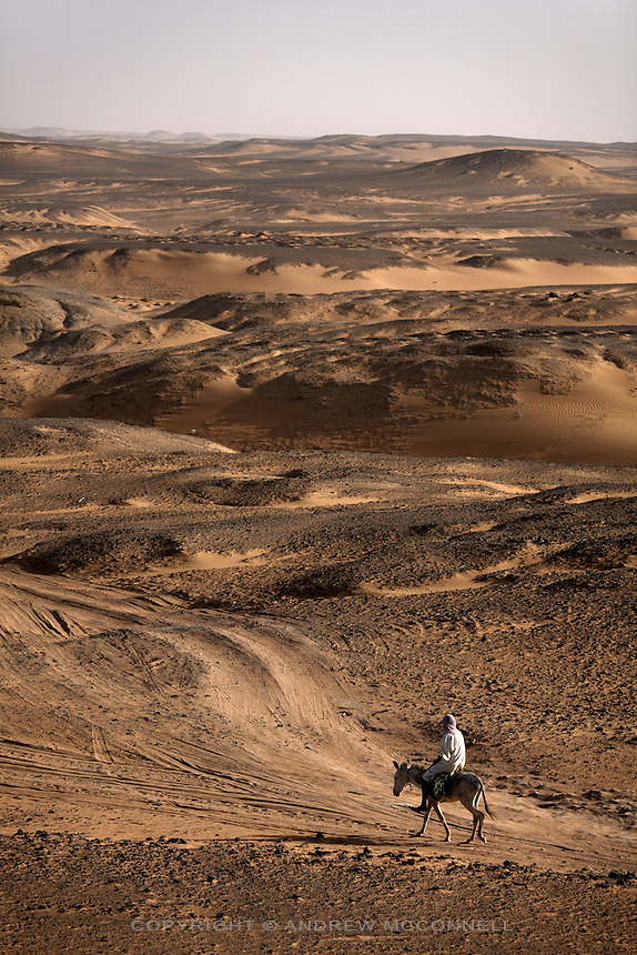 A man on mule-back traverses the desert around the ancient city of Old Dongola, Sudan, on Monday, March 26, 2007.