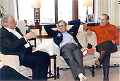 United States President George H.W. Bush, Center, meets informally with Chancellor Helmut Kohl of Germany, left, and United States Secretary of State James A. Baker III, right, at Camp David, Maryland on February 24, 1990.