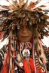 "Head and shoulders portrait of Native American in pow wow regalia, wearing Bird nest headdress at the Thunderbird Pow-Wow in the Queens County Farm Museum, NY ....A pow-wow (also powwow or pow wow or pau wau) is a gathering of North America's Native people. The word derives from the Narragansett word powwaw, meaning ""spiritual leader""."