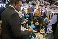 An Uber employee speaks with a visitor at the TechDay New York event on Thursday, April 23, 2015. Thousands attended to seek jobs with the startups and to network with their peers. TechDay bills itself as the world's largest startup event with over 300 exhibitors. (© Richard B. Levine)