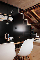 """The wall in this dining room is faced in black linoleum and an open staircase leads to the bedroom above; the dining chairs are the """"Plastic Side Chair"""" design by Charles Eames"""