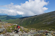 Hiker ascending the Ammonoosuc Ravine Trail in the White Mountains of New Hampshire during the summer months.