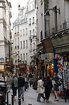 People walking through the narrow confines of  .the latin quarter showing shops,bars, restaurants and apartment buildings. Paris,France