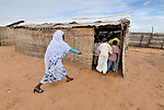 """The school director """"encourages"""" students to get into their classroom on time in the Dereig Camp for internally displaced persons in Sudan's war-torn Darfur region."""