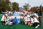 09 November 2014: Wake Forest players and coaches pose with the ACC championship trophy in front of the scoreboard. The Wake Forest University Demon Deacons played the Syracuse University Orange at Jack Katz Stadium in Durham, North Carolina in the 2014 Atlantic Coast Conference NCAA Division I Field Hockey Championship Game. Wake Forest won the game 2-0.