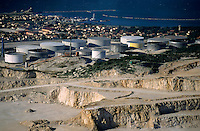 Oil tanks and stone quarry near sea.