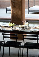 A table is laid for lunch in the covered area of the internal courtyard overlooking the fish pool
