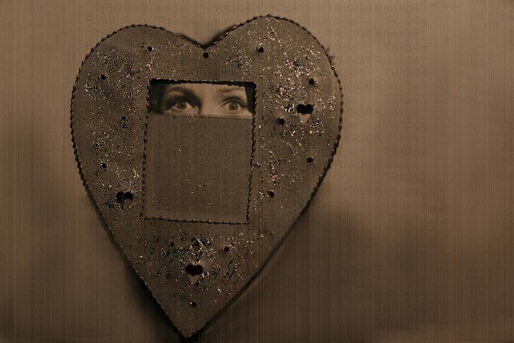 A woman peering through a heart